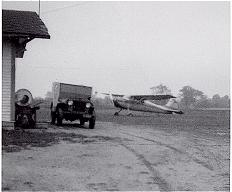 A car and plane at the original Howell Airport.