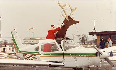 A fake reindeer is mounted on a propeller plane, with Santa Claus as the pilot.