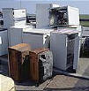 Old household appliances being stacked for recycling.