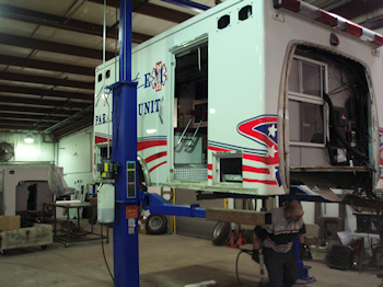 EMS unit on a vehicle lift for repairs.